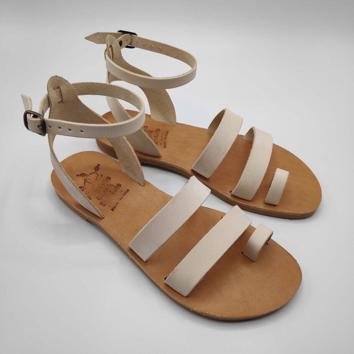 White nubuck leather dressy sandals with two straps, toe ring and high ankle strap, side view