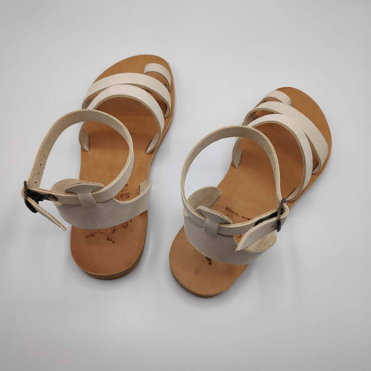 White nubuck leather dressy sandals with two straps, toe ring and high ankle strap, back view