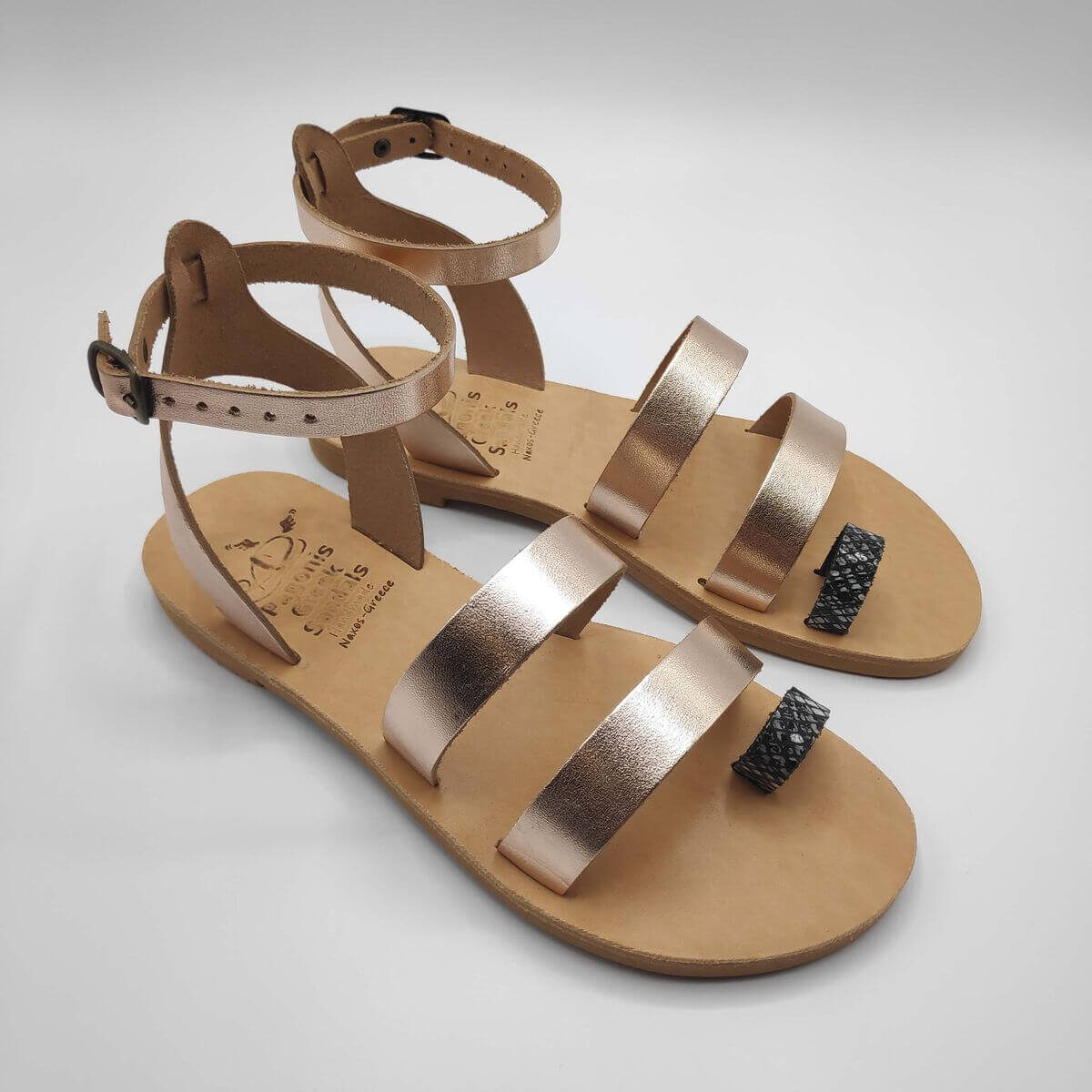 Rose gold leather dressy sandals with two straps, toe ring and high ankle strap, side view