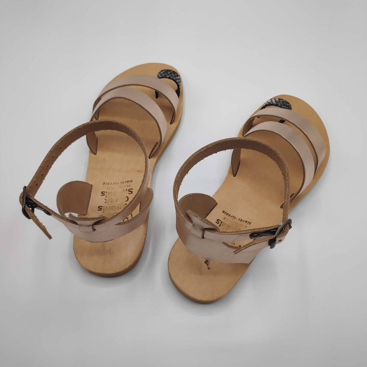 Rose gold leather dressy sandals with two straps, toe ring and high ankle strap, back view