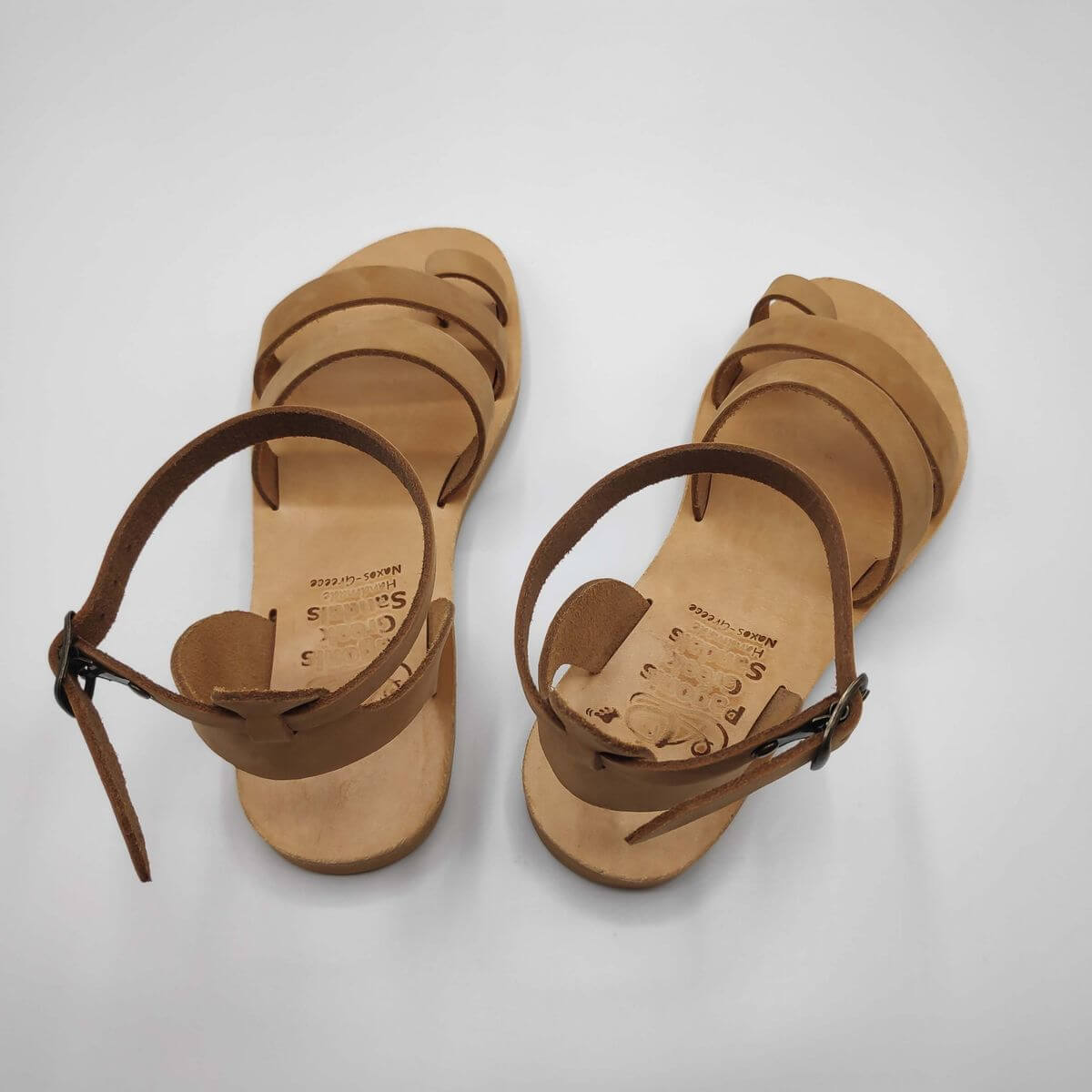 Nude nubuck leather dressy sandals with two straps, toe ring and high ankle strap, back view